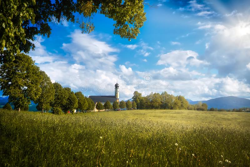 Bavarian idyllic scenary - historic chapel at the Irschenberg and church at the european alps - irschenberg - germany - stock photo