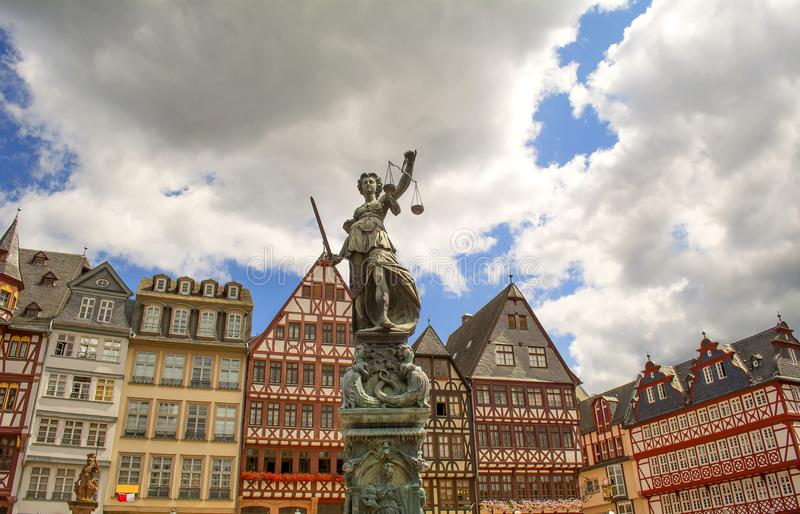 Historic city center of Frankfurt and statue of Justitia holding sword and scales. Half-timbered fachwerk houses in the background. A lot of restaurants and royalty free stock image