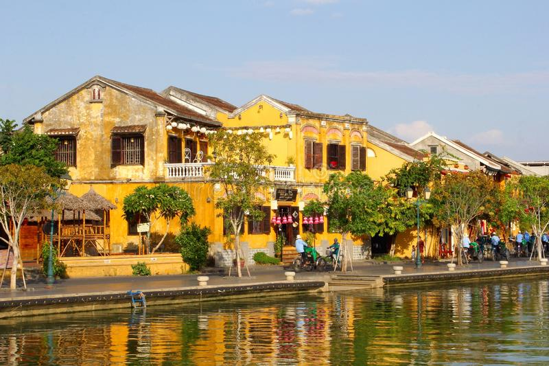 Historic colonial buildings river reflections, Hoi An. Old colonial yellow buildings and houses along the river and reflections in water white people are cycling stock images