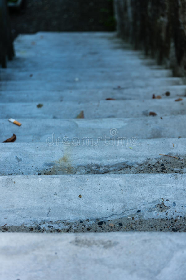 Historic concrete stair downside view with cigarette on floor stock image