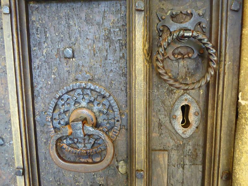 Historic door handles on old wood door. Old metal door handles and keyhole on the oak door of the historic church in the village of East Brent in Somerset royalty free stock photography