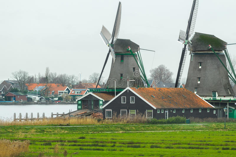 Historic Dutch village with old windmills and river landscape stock image