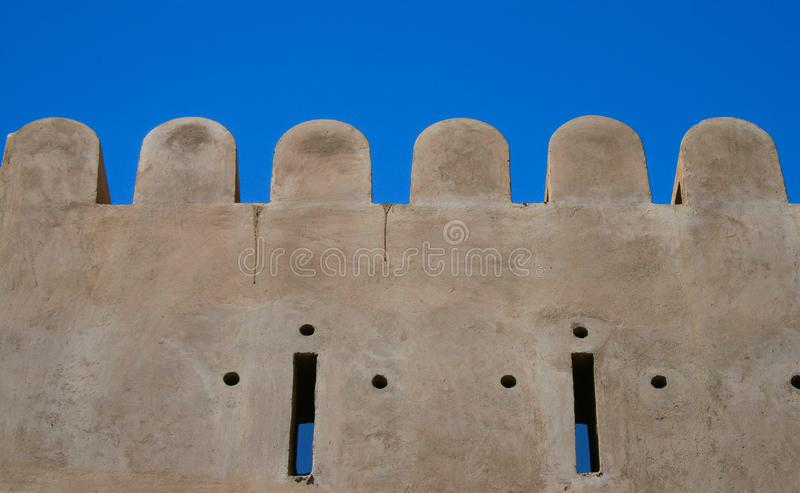 A wall of fort in the Sur city of the Oman royalty free stock image