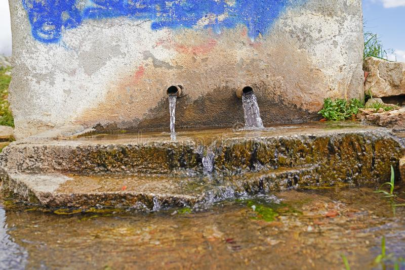 Historic fountain in an old village. Flowing natural spring water royalty free stock images