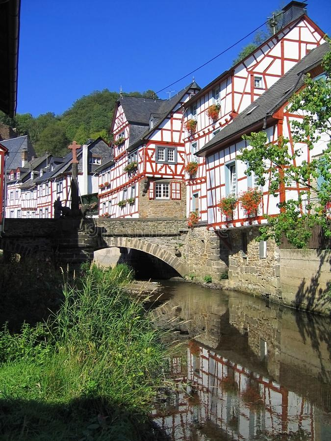 Half-timbered Houses along Elz River in Monreal, Rhineland-Palatinate, Germany. Historic half-timbered houses are reflected in the waters of the Elz River in the stock image