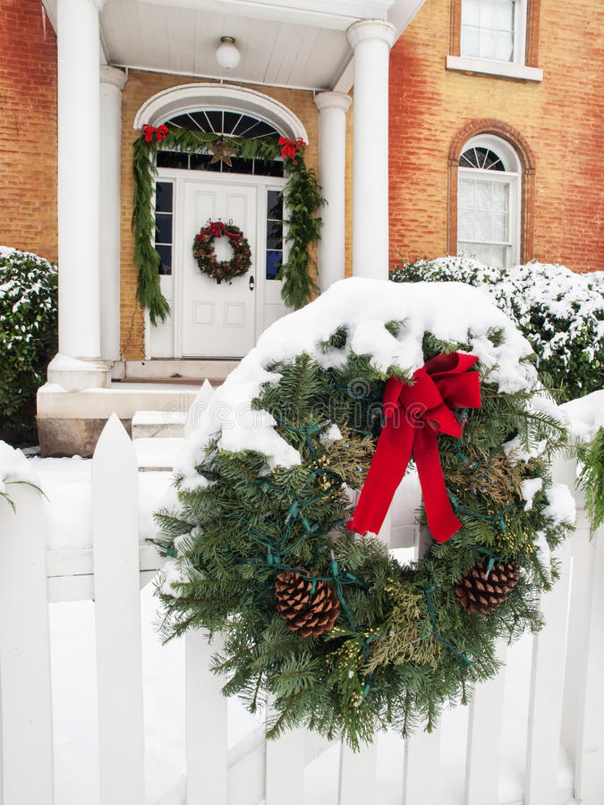 Historic home with Christmas decorations. Historic brick home with pillared porch and Christmas decorations and fresh snow in Jacksonville, Oregon royalty free stock photography