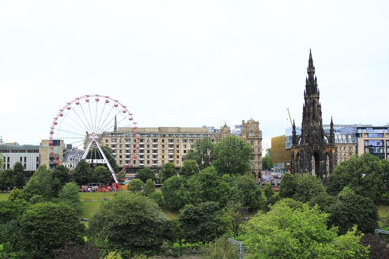 Historic landmark, Scott Monument in the heart of Edinburgh, Scotland with Ferris wheel at annual Fringe Festival. Historic landmark, Scott Monument in the heart royalty free stock photography