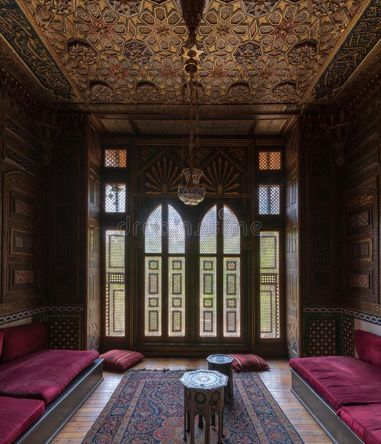 Historic Manial Palace of Prince Mohammed Ali. Small room at reception hall with ornate wooden wall and ceiling, Cairo, Egypt. Historic Manial Palace of Prince royalty free stock images