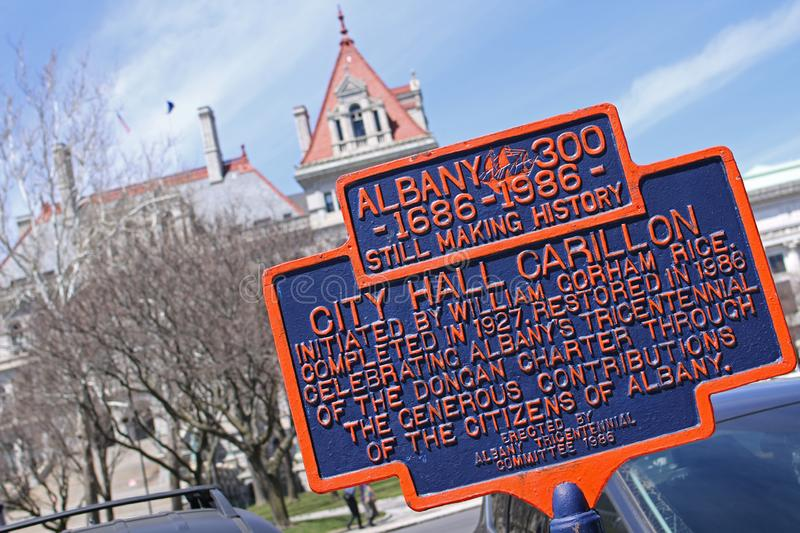 Historic marker for the Albany City Hall Carillon. Blue and orange historic marker for the Albany City Hall carillon in foreground of Albany capital building royalty free stock images