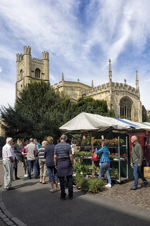 The Historic Market in Market Square overlooked by Great St Mary's Church. CAMBRIDGE, UNITED KINGDOM - Aug 11, 2017: CAMBRIDGE, UK:  The Historic Market in royalty free stock photos