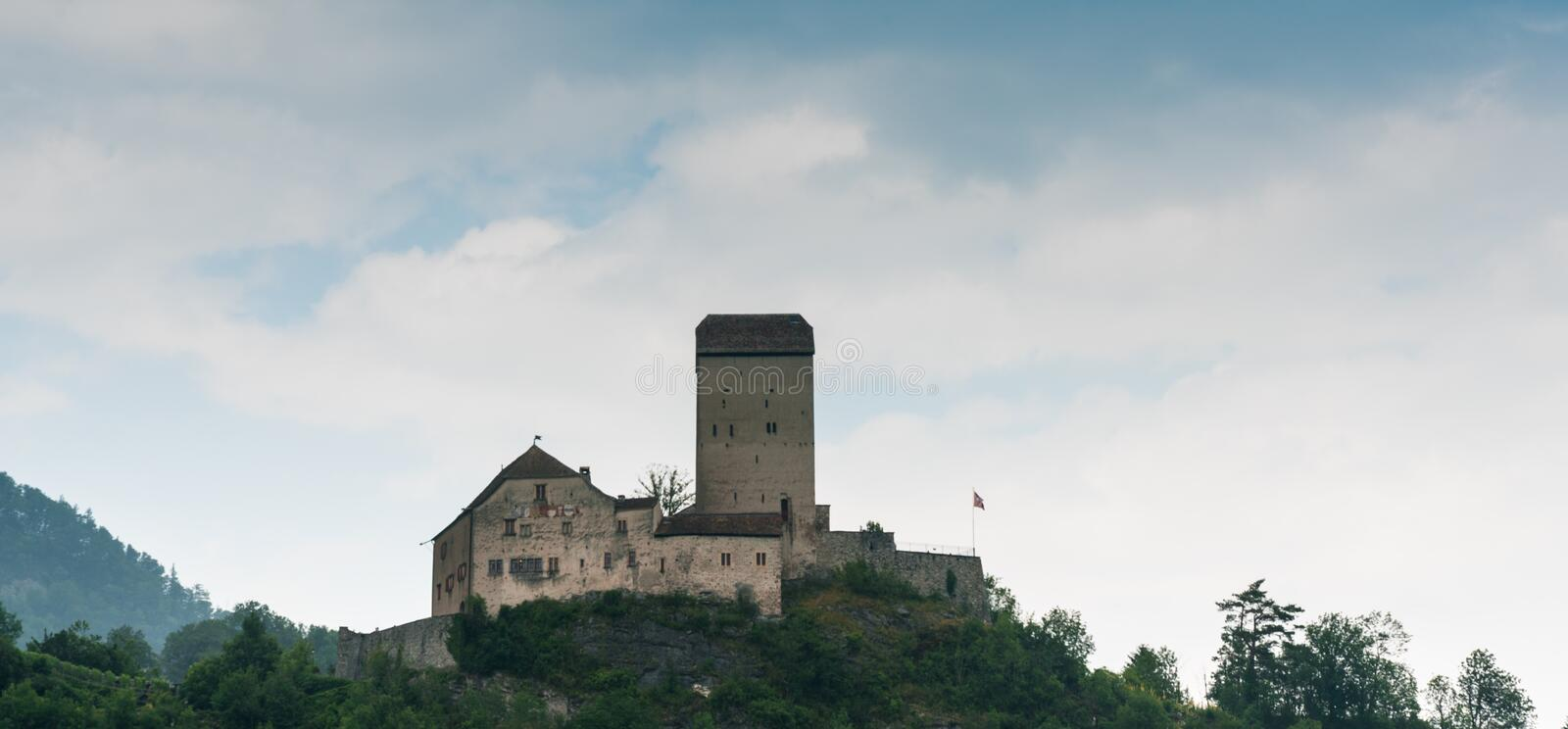 The historic medieval castle at Sargans in the southeastern Swiss Alps on its grassy hilltop promontory. Sargans, SG / Switzerland - 9. July 2019: the historic royalty free stock image