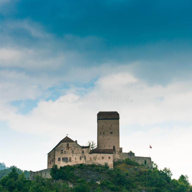 The historic medieval castle at Sargans in the southeastern Swiss Alps on its grassy hilltop promontory. Sargans, SG / Switzerland - 9. July 2019: the historic royalty free stock images