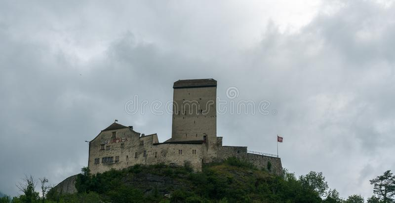 The historic medieval castle at Sargans in the southeastern Swiss Alps on its grassy hilltop promontory. Sargans, SG / Switzerland - 9. July 2019: the historic stock photo