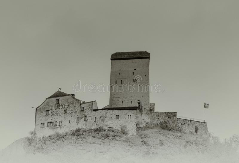 The historic medieval castle at Sargans in the southeastern Swiss Alps on its grassy hilltop promontory. Sargans, SG / Switzerland - 9. July 2019: the historic stock photography