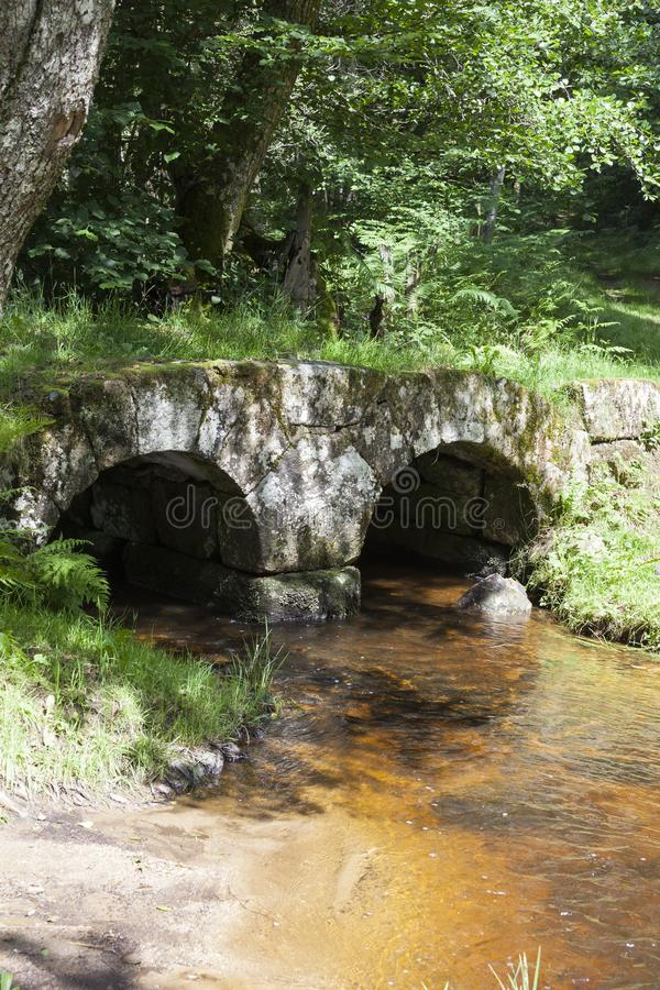 The historic medieval stone Pont de Poupee in the forests near Valliere, Creuse, Nouvelle-Aquitaine, France, a Gallo-Roman bridge. The historic medieval stone stock image