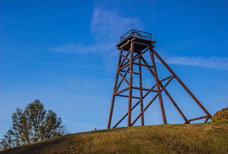 Historic mining tower on top of hill. Historic mining tower with platform & wheel on top of a hill royalty free stock images