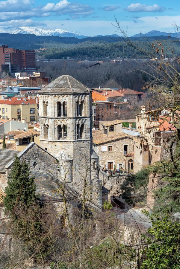 Historic Monastery in Girona, Spain. Vertical view of historic Sant Pere de Galligants Monastery with the Pyrenees Mountains in the background royalty free stock photography
