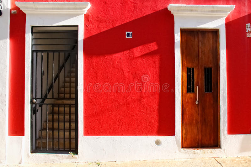 Historic Old San Juan - Red Walls, Doors, Stairs. A medium brown door and gated staircase set against a rich red wall wall provide a beautiful view of Old San royalty free stock images