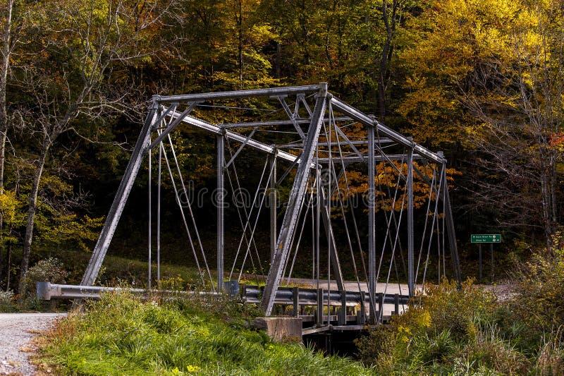 Historic Pratt Truss Bridge - East Fork Greenbrier River, West Virginia. An autumn view of a historic one-lane Pratt through truss bridge over the East Fork royalty free stock photo