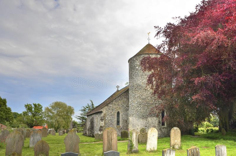 Historic Round Tower Church of East England. View of the historic round tower church and graveyard of All Saints, Freethorpe, Norfolk, England stock photography