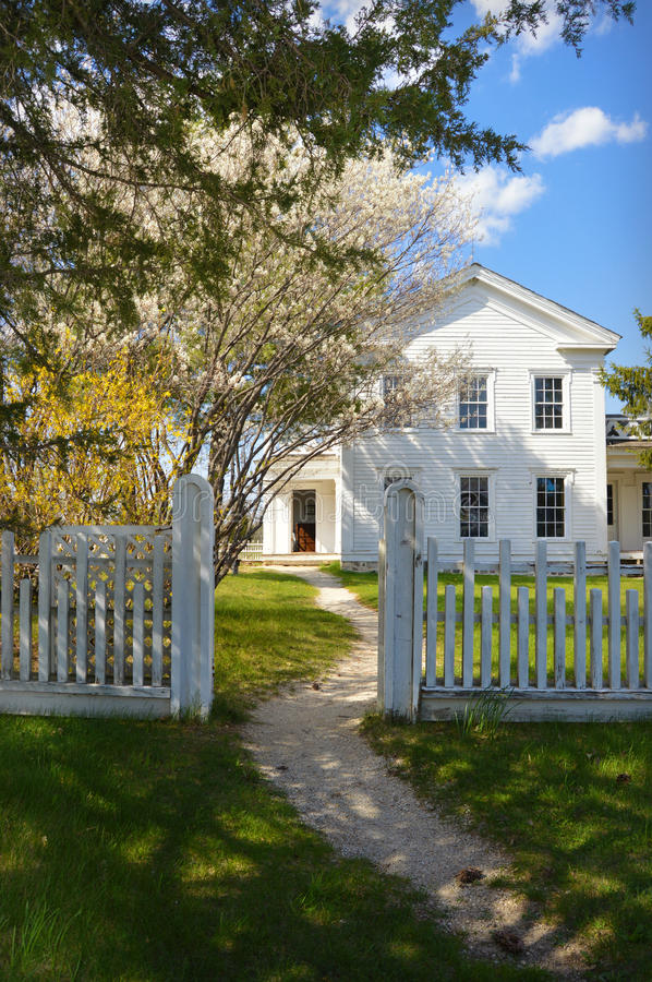 Historic Sanford House. The historic Sanford house at Old World Wisconsin. A pathway leads through the white picket fence, past flowering forsynthia bushes and stock image