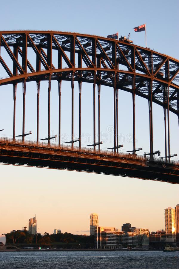 Historic steel truss arch bridge with crane, Australian and New South Wales flags on top. Iconic Sydney Harbor Bridge at dusk. Middle section of bridge royalty free stock images
