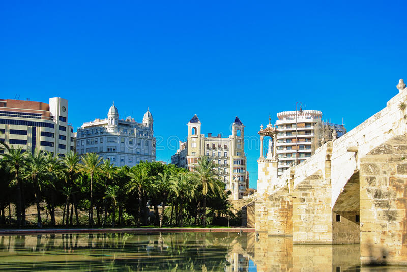 A historic stone bridge Puente Del Mar and a pond near it with residential apartment buildings and a row of palms in the center of stock images