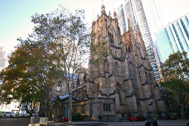 Historic stone gothic revival church building of St Andrew`s Cathedral next to urban high-rise towers in CBD stock photos