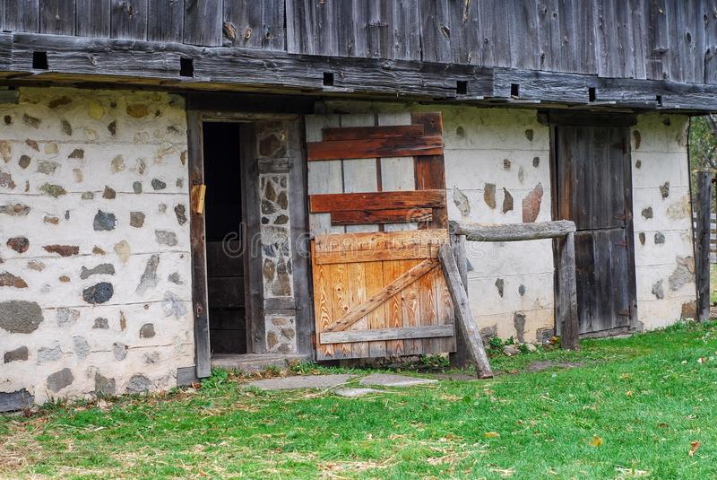 Historic Stone and Post and Beam Barn at Old World Wisconsin. A Historic stones post and beam barn at Old world Wisconsin. Door leaning open and weathered logs royalty free stock photography