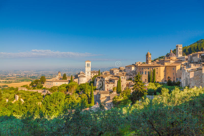 Historic town of Assisi at sunrise, Umbria, Italy. Panoramic view of the historic town of Assisi in beautiful golden morning light at sunrise in summer, Umbria stock photos