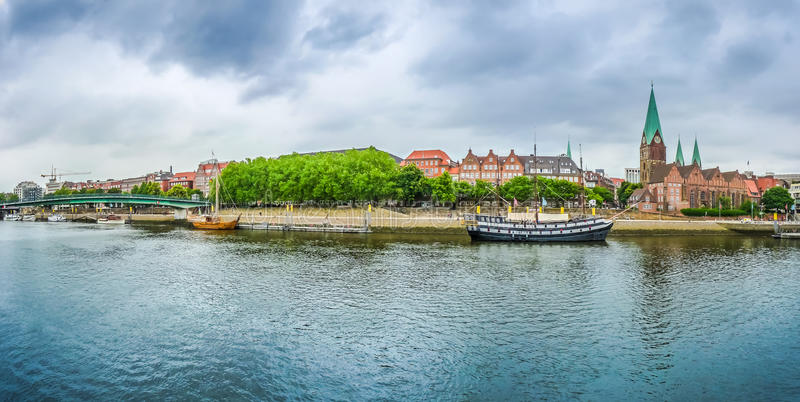 Historic town of Bremen with Weser river, Germany. Historic town of Bremen with old sailing ship on Weser river and dramatic cloudscape, Germany stock photos
