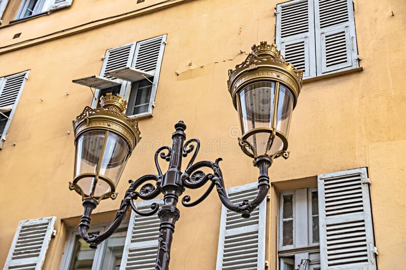 Historic two-armed street lamp in Nice, France, in front of a house facade. With wooden shutters royalty free stock photos