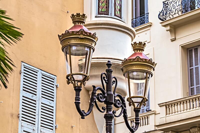 Historic two-armed street lamp in Nice, France, in front of a house facade. With wooden shutters royalty free stock photo