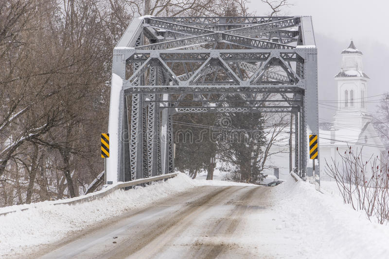 Historic West Creek Truss Bridge - New York. A snowy view of the historic Warren through truss over West Creek in Tioga County, New York. A white sided church is stock photos