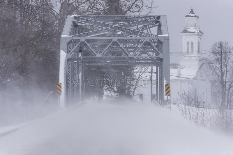 Historic West Creek Truss Bridge - New York. A snowy view of the historic Warren through truss over West Creek in Tioga County, New York. A white sided church is stock image