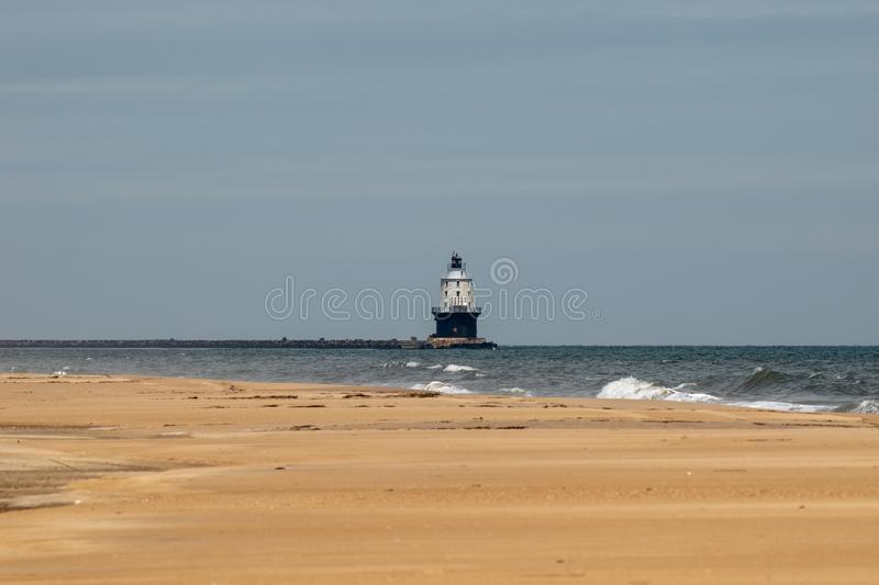 White Lighthouse on the Atlantic Ocean. A historic white lighthouse on the Atlantic Ocean seen from the beach at Cape Henlopen royalty free stock image