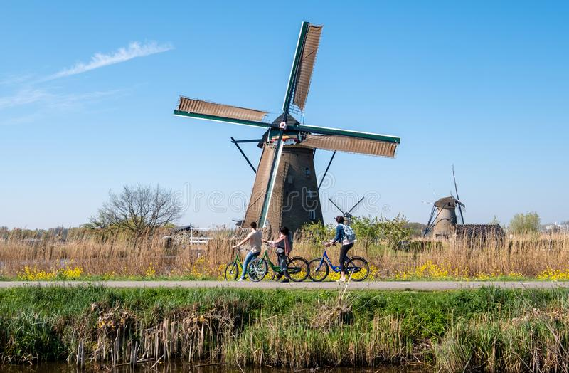 Historic windmill with cyclists in foreground, at Kinderdijk, Holland, Netherlands, a UNESCO World Heritage Site. royalty free stock photo