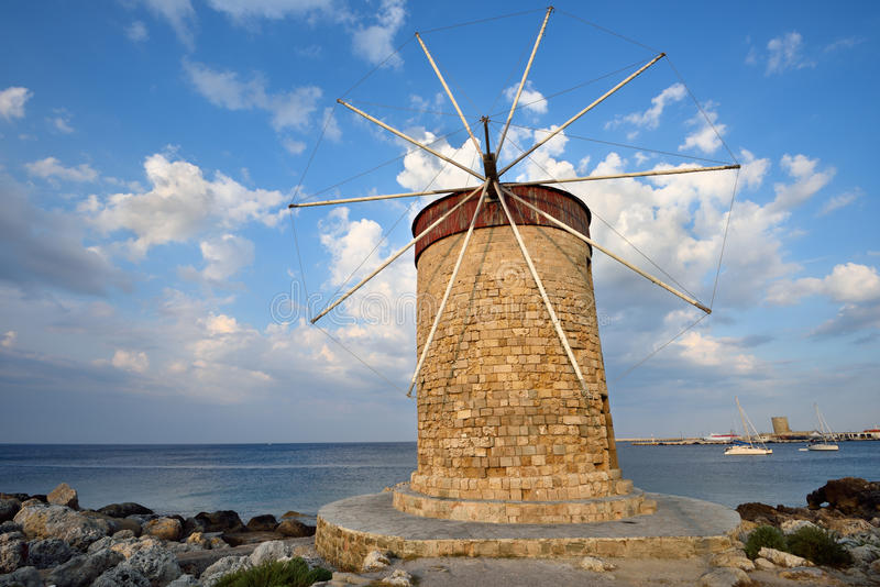 Historic windmill by the sea. Historic windmill in the Mandraki harbour on Rhodes island in Greece stock photos