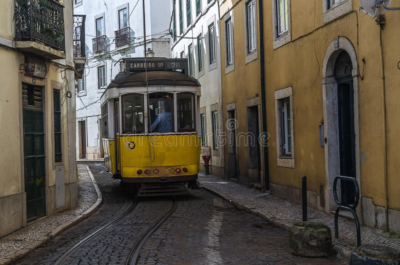 Historic yellow tram 28, famouse tourist attraction, in narrow street of Lisbon,Portugal. Historic yellow tram 28, famouse tourist attraction, in narrow street stock images
