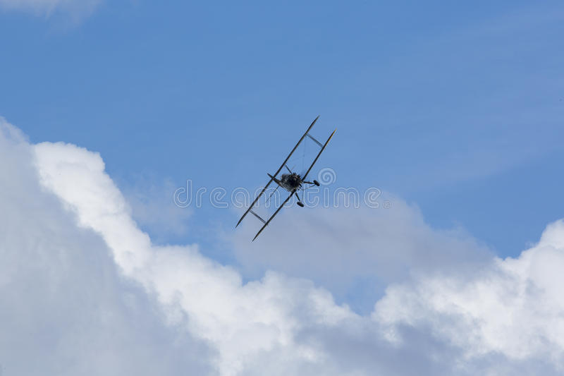 Historical airplane doing manoeuvres in the sky. Veteran pilot with a veteran plane against a blue sky stock photo