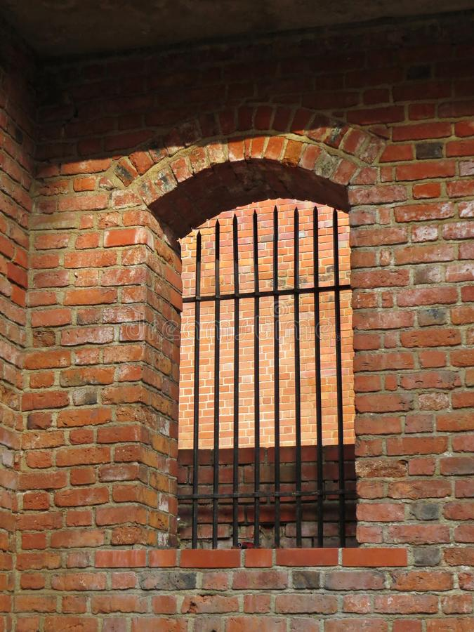 Historical Arched Window with Iron Bars on Red Brick Wall. Historical Arched Window with Iron Bars on a Red Brick Wall stock photos