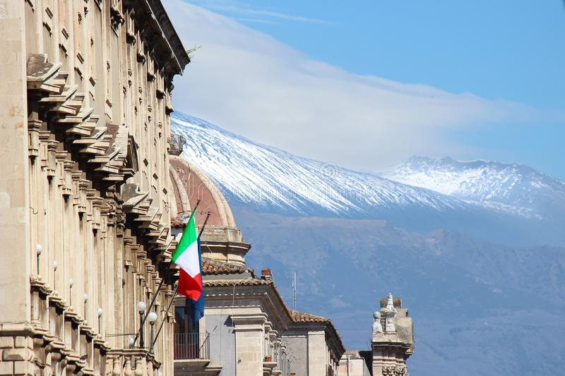 Historical building in Catania, Sicily, Italy with waving Italian flag. In the background cupola of famous Saint Agatha Cathedral. And Mount Etna with snow on stock image