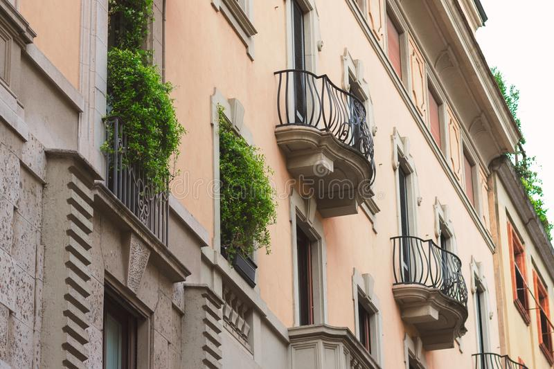 Historical building with greens on balconies. Milan, Italy royalty free stock photography