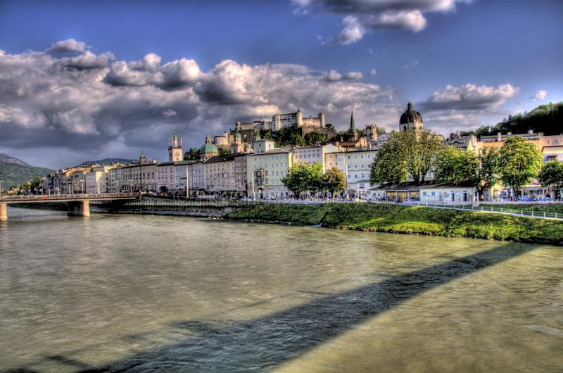 Historical buildings beside a river in salzburg, a royalty free stock image