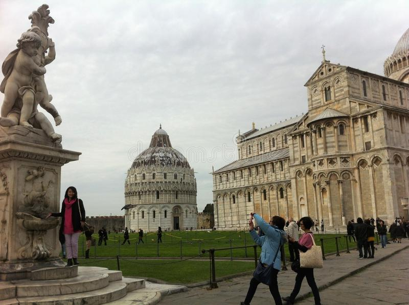 The historical center of Pisa. Architectural ensemble. Tourists are photographed at the monuments. stock photos