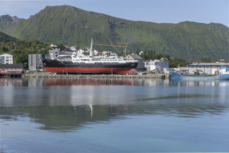 Historical coastal cruiser ashore on embankment at Stokmarknes, Norway. STOKMARKNES NORWAY July 09 2019: cityscape with historical coastal cruiser ashore on royalty free stock photos