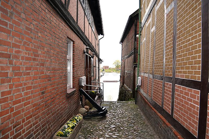 Historical cobblestone alley with half-timbered houses at a rainy day royalty free stock images