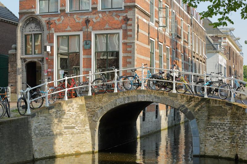 Historical facades located along Oude Delft Canal, with Breestraat Bridge in the foreground royalty free stock photo