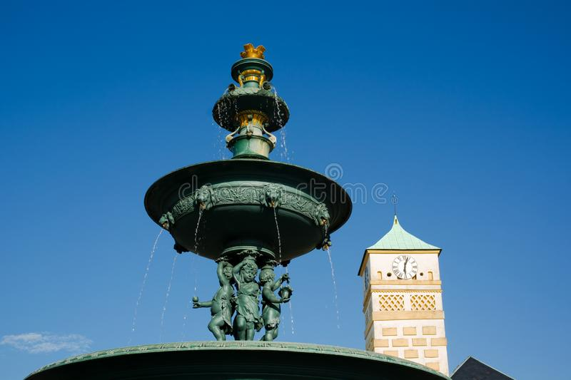 Historical fountain made of cast iron, Masaryk square, Karvina, Czech Republic / Czechia. Landmark and monument, building of town hall and clear blue sky royalty free stock image