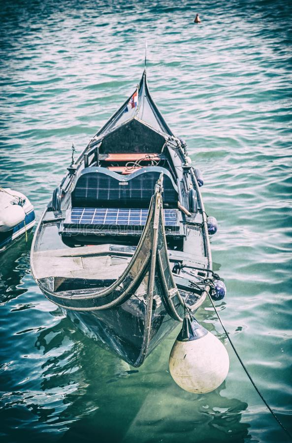 Historical gondola in harbor, Split, analog filter. Historical gondola in harbor, Split, Croatia. Summer vacation. Travel destination. Analog photo filter with royalty free stock image